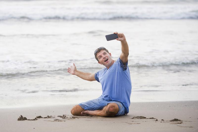 Homem atrativo e feliz novo do Caucasian 30s que tem o divertimento na praia asiática que toma a imagem do selfie com o sorriso d foto de stock