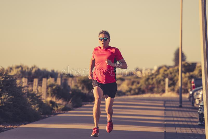 Homem atrativo e feliz novo do corredor do esporte com ajuste e treinamento saudável forte do corpo fora da trilha da estrada no  imagem de stock