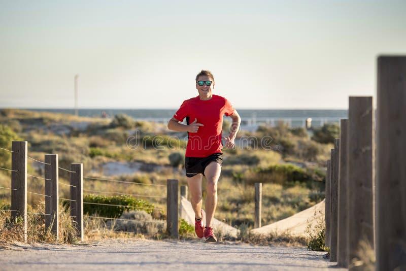 Homem atrativo e feliz novo do corredor do esporte com ajuste e treinamento saudável forte do corpo fora da trilha da estrada no  imagem de stock royalty free