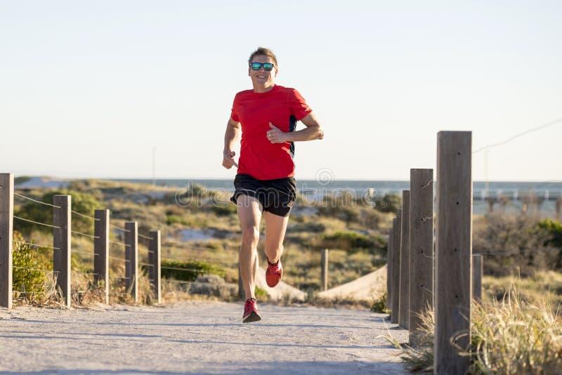 Homem atrativo e feliz novo do corredor do esporte com ajuste e treinamento saudável forte do corpo fora da trilha da estrada no  imagens de stock royalty free