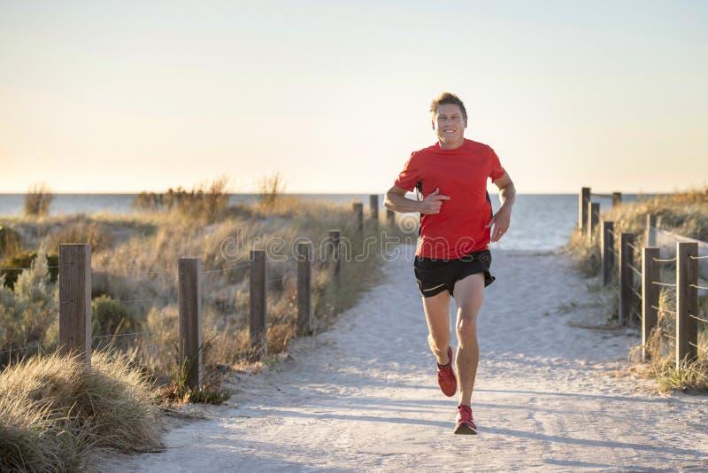 Homem atrativo e feliz novo do corredor do esporte com ajuste e treinamento saudável forte do corpo fora da trilha da estrada no  fotografia de stock royalty free