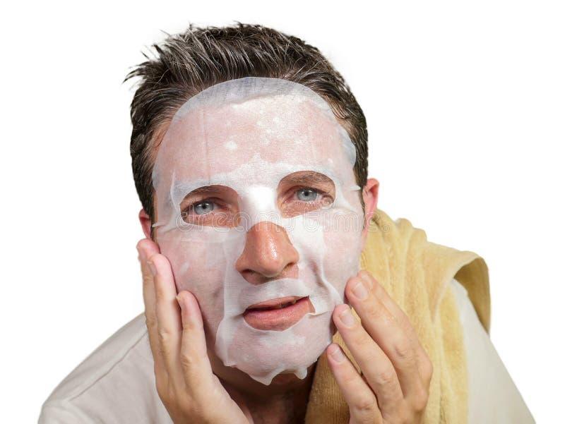 Homem atrativo e feliz novo que usa a máscara facial do papel da beleza que toca em sua cara que olha ao sorriso do espelho alegr imagem de stock