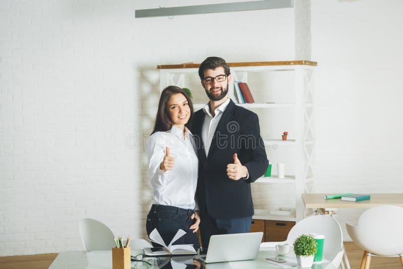 Homem atrativo e mulher que mostram os polegares acima foto de stock royalty free
