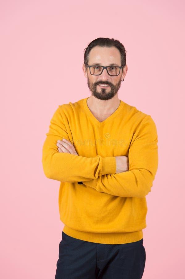 Homem atrativo no casaco de lã e nos vidros com mãos cruzadas no retrato da caixa do homem seguro considerável no estúdio imagens de stock