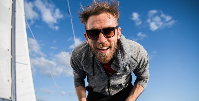 Homem atrativo nos óculos de sol no iate Retrato próximo de uma cara louca feliz, riso atrativo do yachstman do desportista imagens de stock