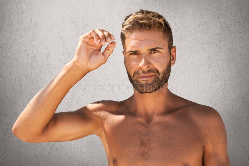 Homem atrativo novo com a aparência atraente que está despida, levantando sua mão, mostrando seu bíceps Homem macho à moda que le fotos de stock