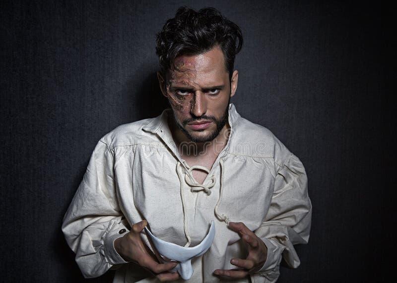 Homem atrativo novo com as cicatrizes das queimaduras, guardando um teatro branco como a máscara imagens de stock royalty free