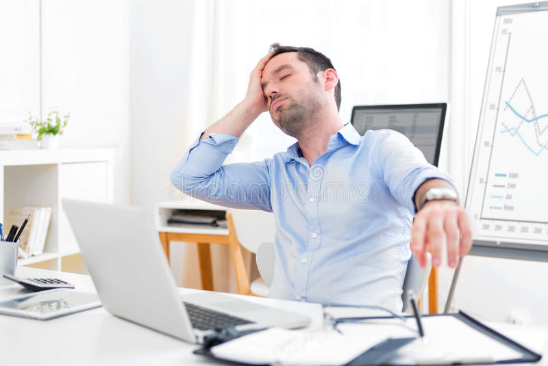 Homem atrativo novo demasiado cansado para trabalhar fotografia de stock