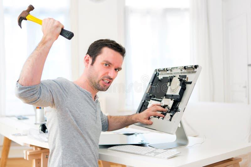 Homem atrativo novo irritado contra o computador imagens de stock royalty free