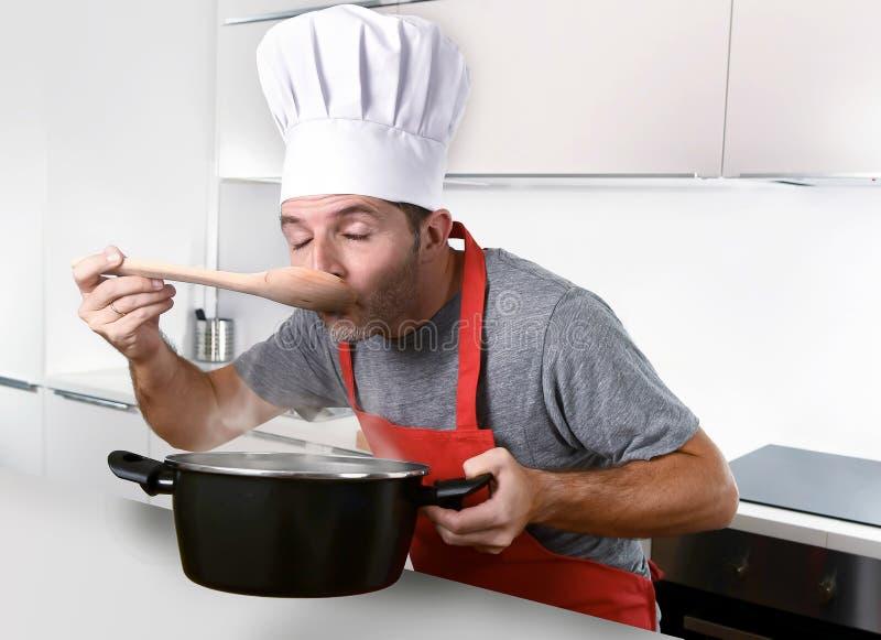 Homem atrativo novo no chapéu do cozinheiro chefe e no sabor vermelho dos testes do avental do cozinheiro imagem de stock royalty free
