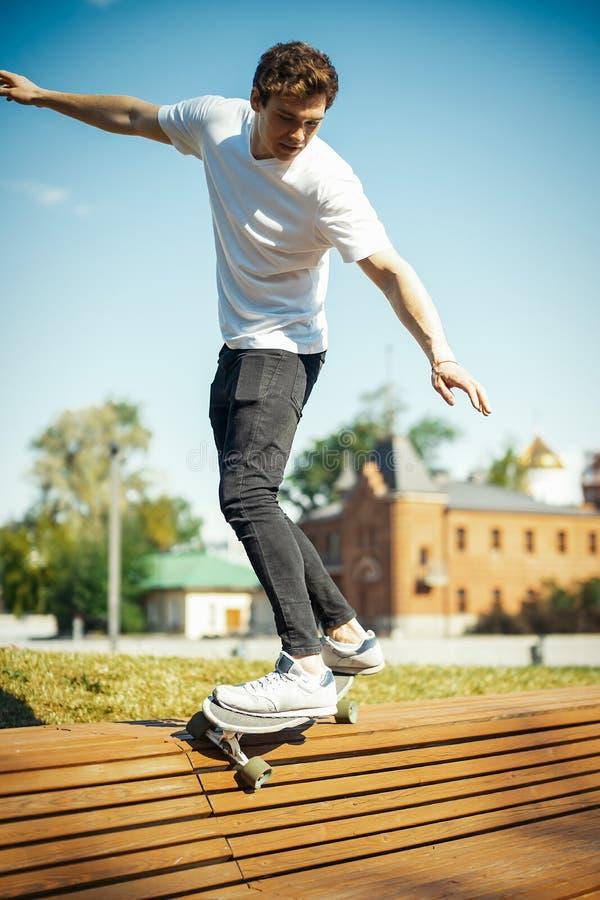 Homem atrativo novo no longboard branco da equitação do t-shirt no parque imagem de stock royalty free