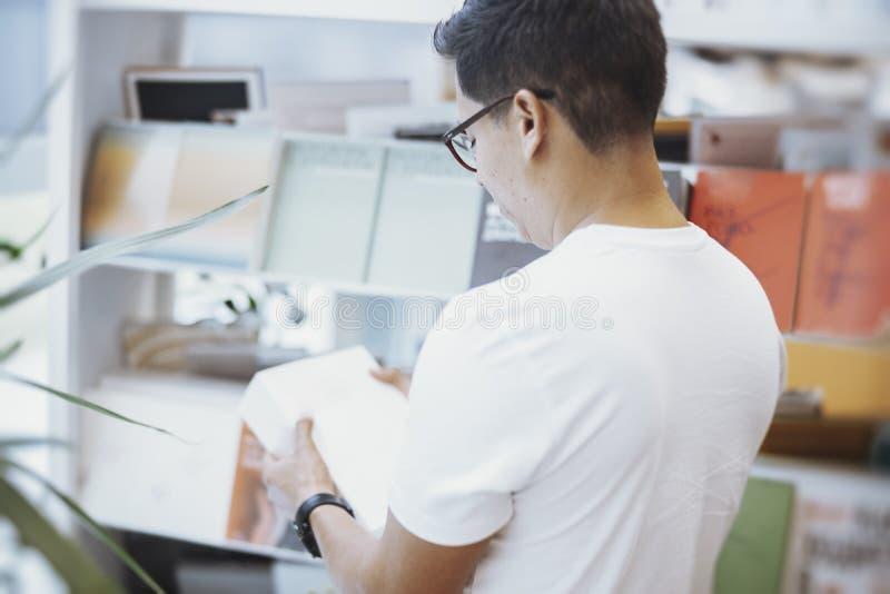 Homem atrativo novo no t-shirt branco que guarda um livro fotos de stock
