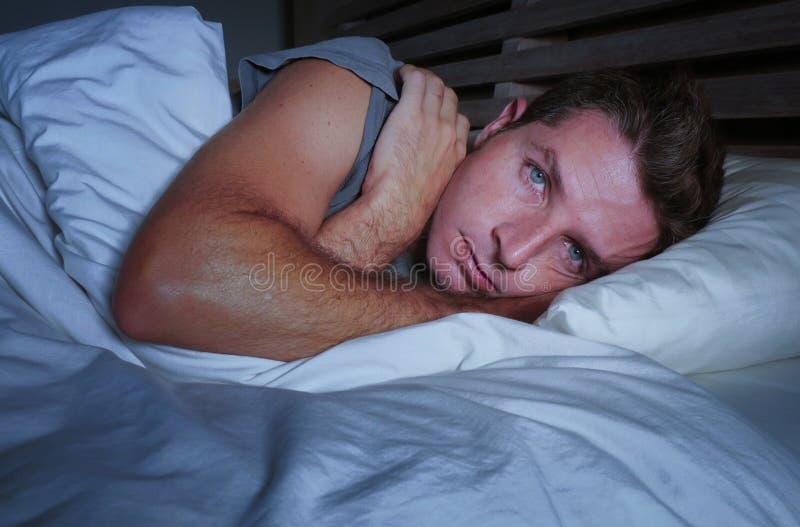 Homem atrativo novo preocupado agitado acordado na noite que encontra-se na cama sem sono com o diso de sofrimento aberto largo d imagem de stock