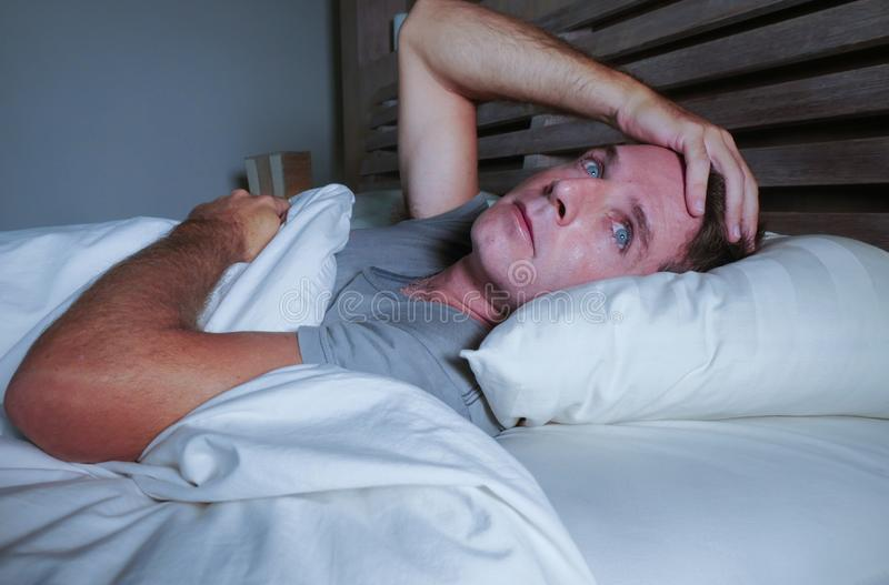 Homem atrativo novo preocupado agitado acordado na noite que encontra-se na cama sem sono com o diso de sofrimento aberto largo d imagem de stock royalty free