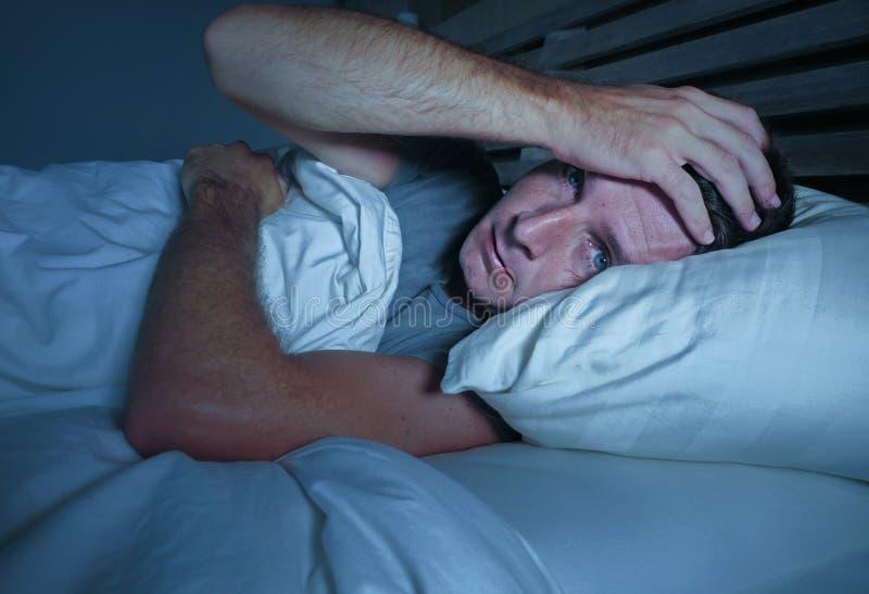 Homem atrativo novo preocupado agitado acordado na noite que encontra-se na cama sem sono com o diso de sofrimento aberto largo d fotografia de stock
