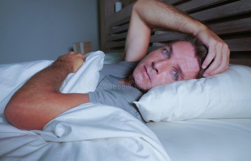 Homem atrativo novo preocupado agitado acordado na noite que encontra-se na cama sem sono com o diso de sofrimento aberto largo d foto de stock