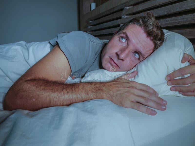 Homem atrativo novo preocupado agitado acordado na noite que encontra-se na cama sem sono com o diso de sofrimento aberto largo d imagens de stock