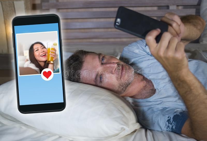 Homem atrativo novo que encontra-se na cama na linha que procuram pelo sexo ou no amor que encontra um perfil bonito da menina en foto de stock royalty free