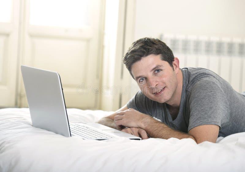 Homem atrativo novo que encontram-se na cama ou sofá que aprecia trabalhos em rede sociais usando o portátil do computador em cas foto de stock