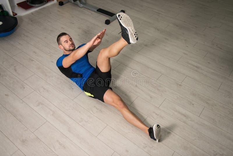 Homem atrativo que executa o exercício abdominal no assoalho foto de stock