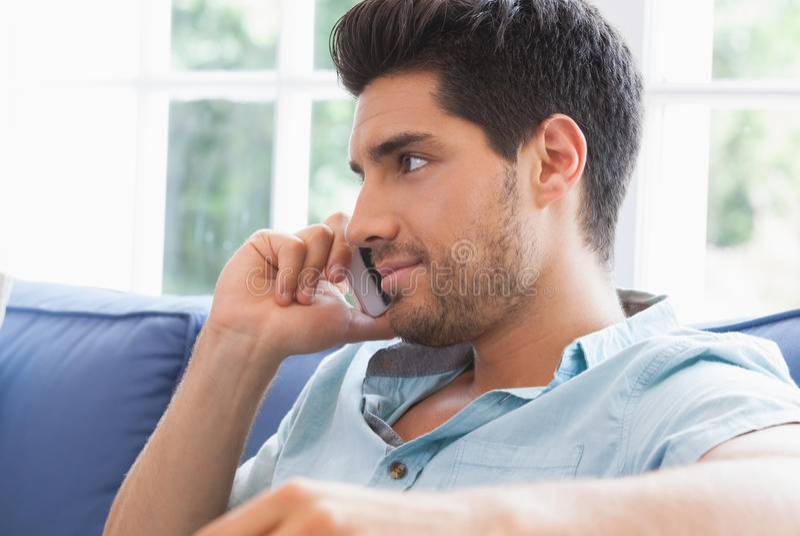 Homem atrativo que faz chamar o sofá fotografia de stock