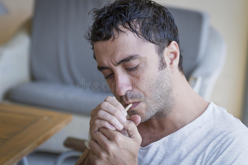 Homem atrativo que ilumina um cigarro fotografia de stock royalty free