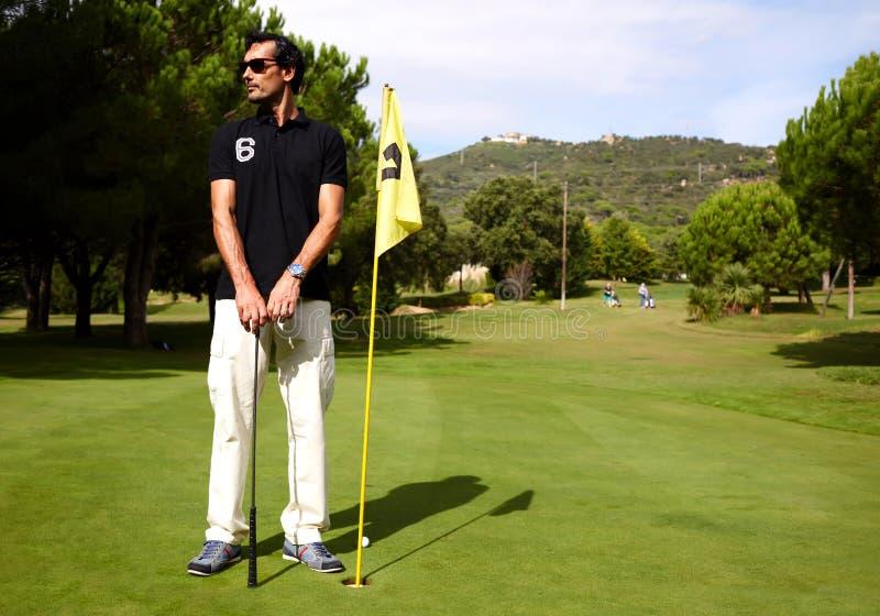 homem atrativo que joga o golfe em um dia de verão morno foto de stock
