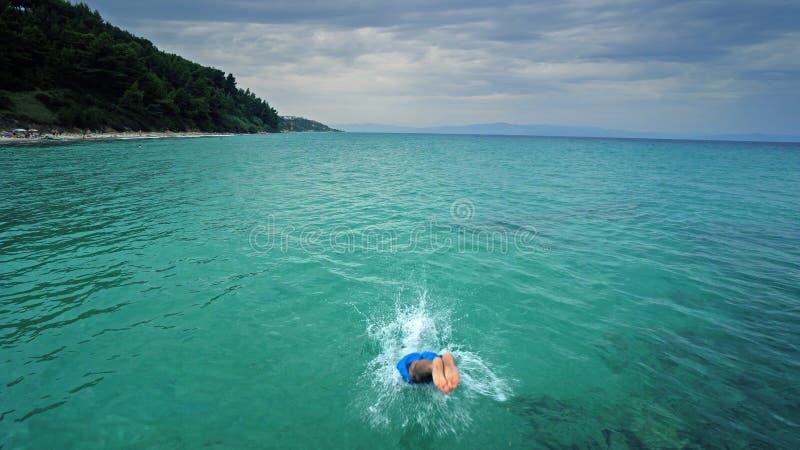 Homem atrativo que salta na água do mar limpa imagens de stock royalty free
