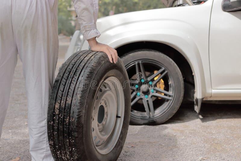Homem automotivo do mecânico que leva o pneu de reposição que prepara a mudança uma roda do carro Serviço de reparação de automóv fotografia de stock