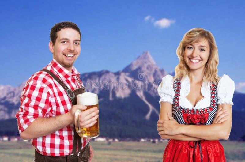 Homem bávaro com caneca de cerveja e mulher do louro com celebrat do dirndl foto de stock royalty free