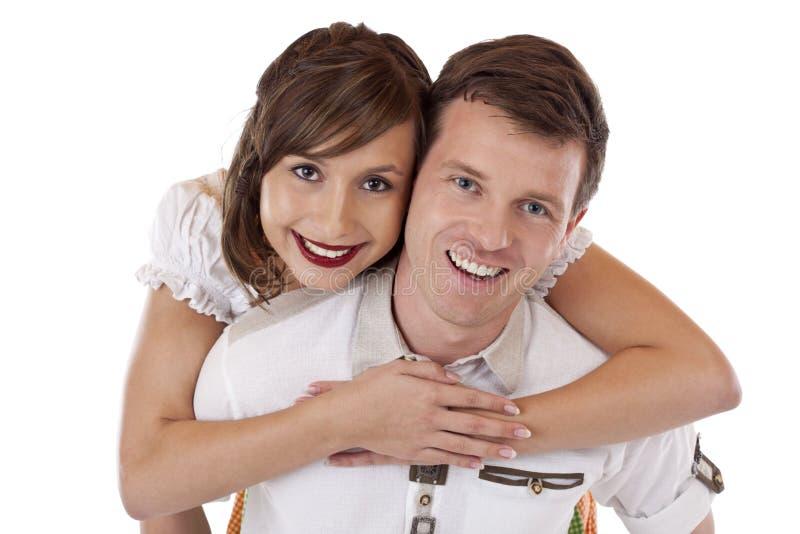 Homem bávaro de sorriso feliz na mulher levando do amor fotografia de stock