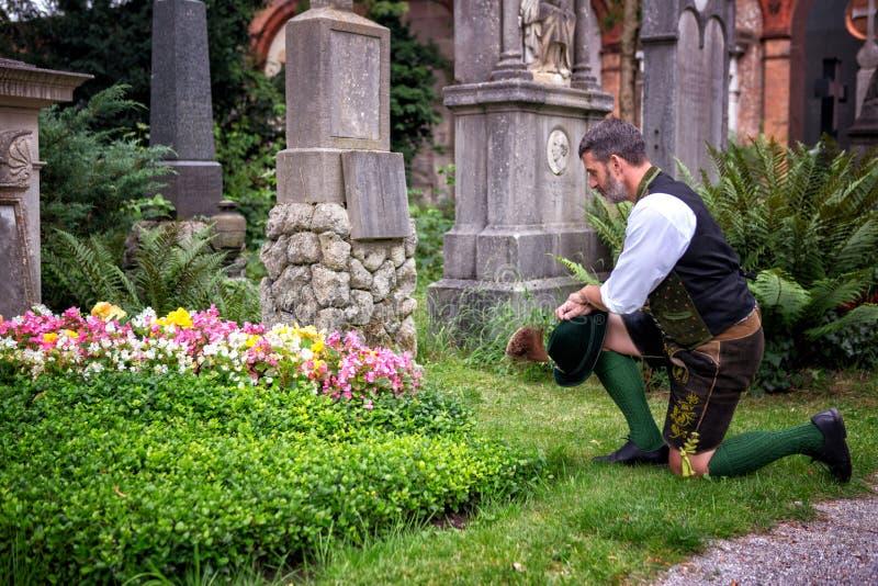 Homem bávaro que ajoelha-se na frente da sepultura fotos de stock royalty free