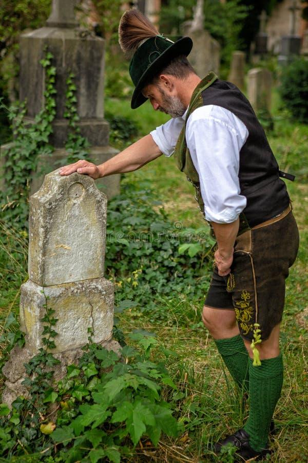 Homem bávaro que está na frente da sepultura imagem de stock royalty free