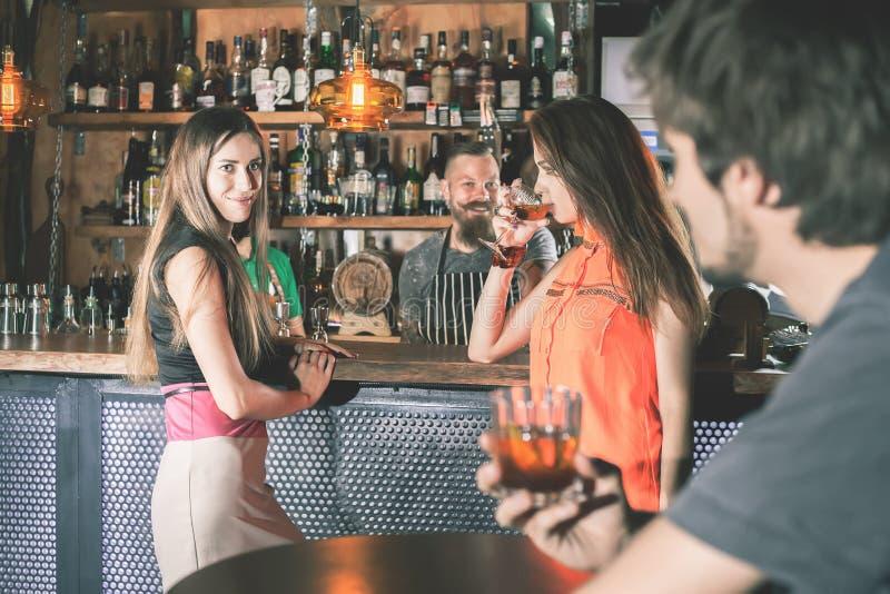 Homem bêbado que senta-se na barra, cocktail bebendo, olhando meninas fotografia de stock