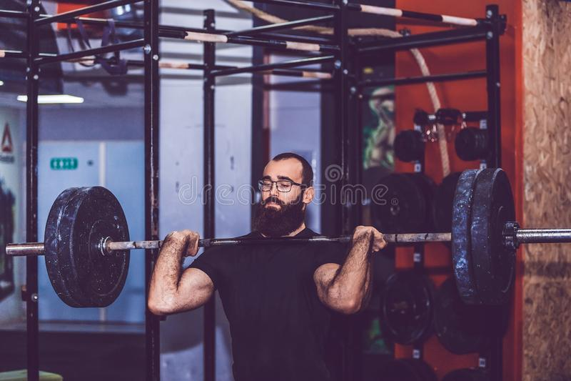 Homem barbudo se esforçando para levantar pesos pesados durante uma sessão de exercícios em uma academia foto de stock