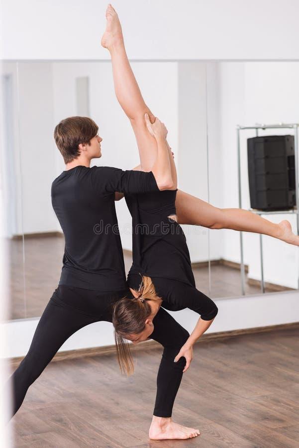 Homem bem construído bonito que guarda seu sócio fêmea da dança fotografia de stock royalty free