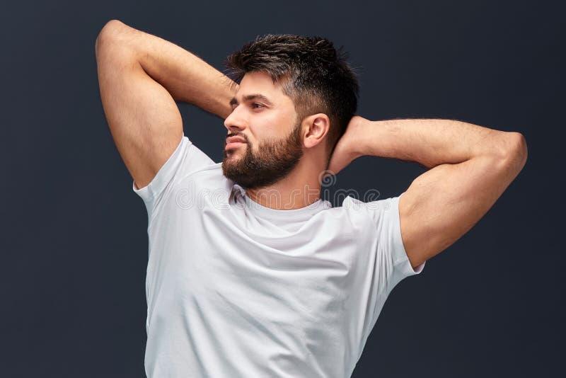 Homem bem-construído brutal considerável forte com os braços aumentados que olham de lado imagem de stock