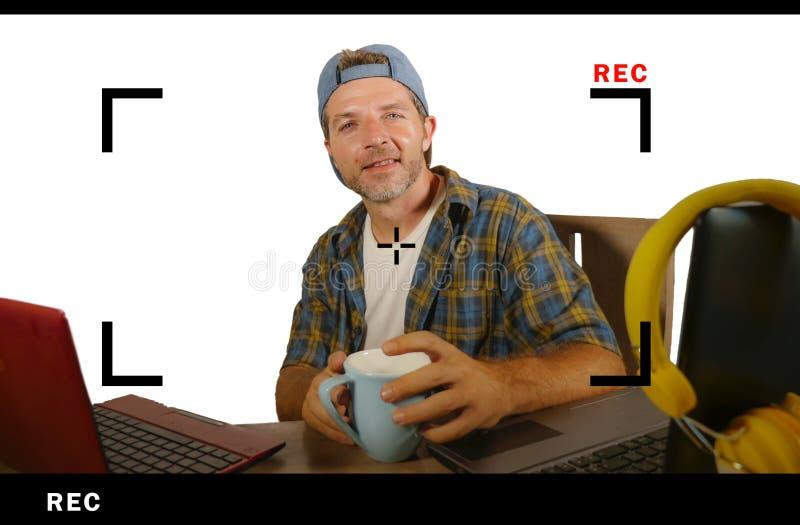 Homem bem sucedido atrativo e feliz do blogger do Internet no tampão americano durante a alimentação em linha que explica e que r foto de stock royalty free