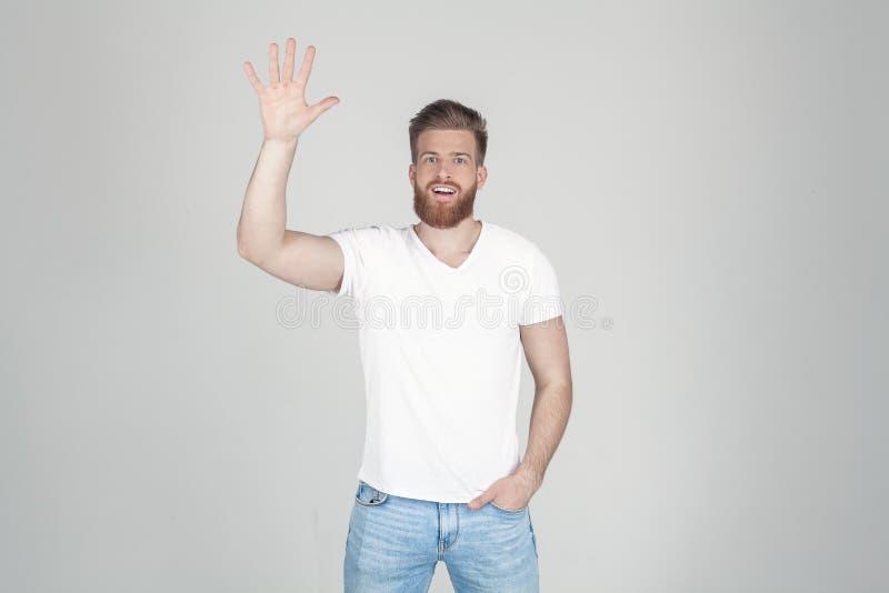 Homem bem sucedido com a barba lux?ria do gengibre acenando sua m?o na c?mera vestida em um t-shirt branco e na cal?as de ganga e fotografia de stock