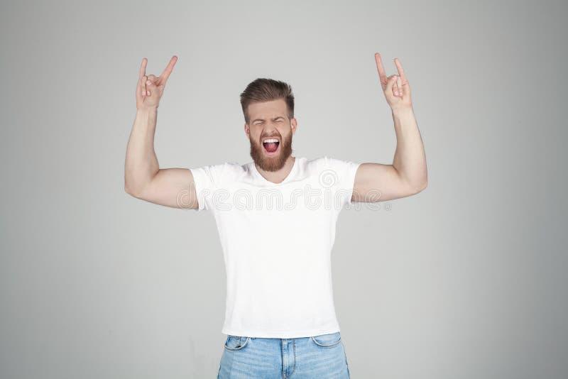 Homem bem sucedido com a barba lux?ria do gengibre gritando com m?os levantadas com um sinal da rocha, suporte na frente do fundo foto de stock royalty free