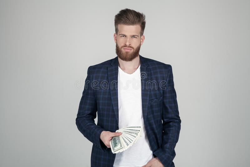Homem bem sucedido com a barba lux?ria do gengibre guarda uns blocos distribu?dos do dinheiro Vestido em um terno suporte na fren imagem de stock