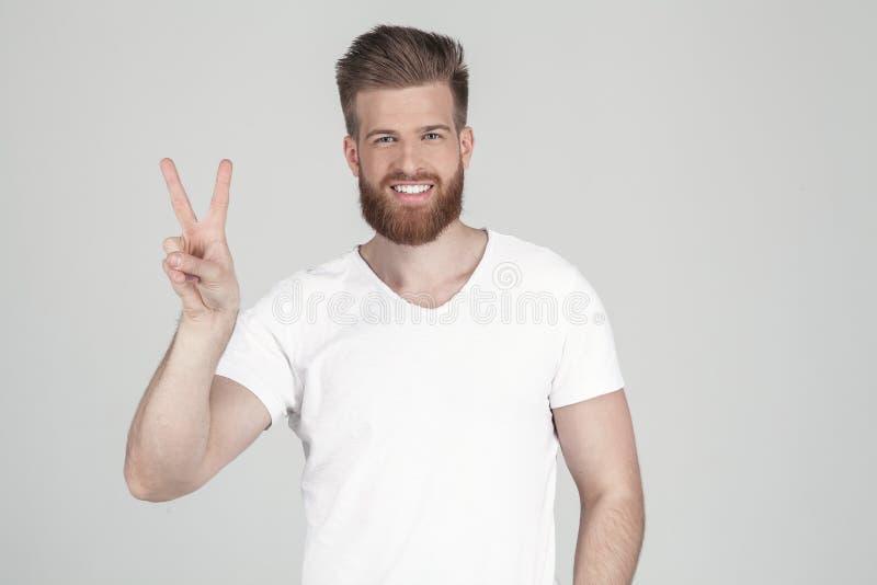 Homem bem sucedido com a barba lux?ria do gengibre sorrisos e mostras um sinal da vit?ria ? c?mera vestido em um t-shirt branco e foto de stock