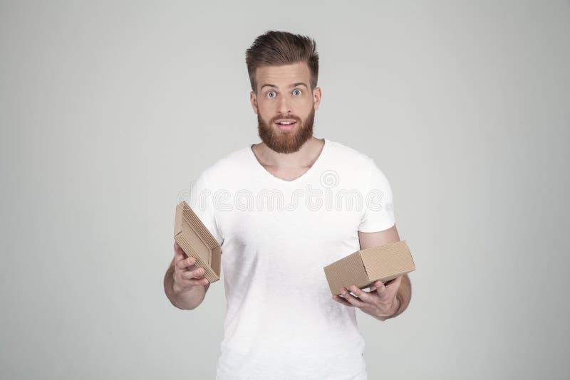 Homem bem sucedido com a barba lux?ria do gengibre surpreendido abre uma caixa com um presente e a vista ? c?mera vestindo um t-s fotografia de stock