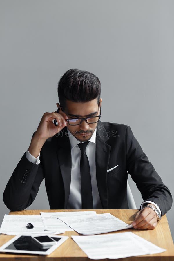 Homem bem sucedido com os vidros que olham seus originais ao sentar-se na mesa de escritório no fundo cinzento foto de stock royalty free