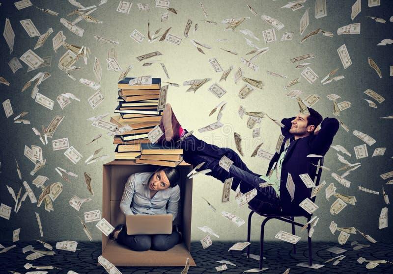 Homem bem sucedido que relaxa sob a chuva do dinheiro com a mulher que trabalha no computador dentro da caixa imagens de stock royalty free