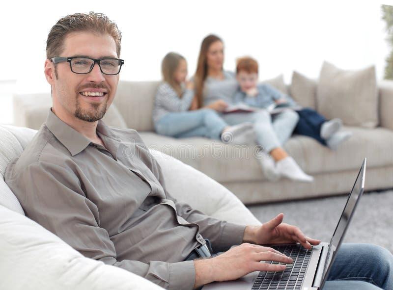 Homem bem sucedido que usa um portátil em sua sala de visitas imagens de stock