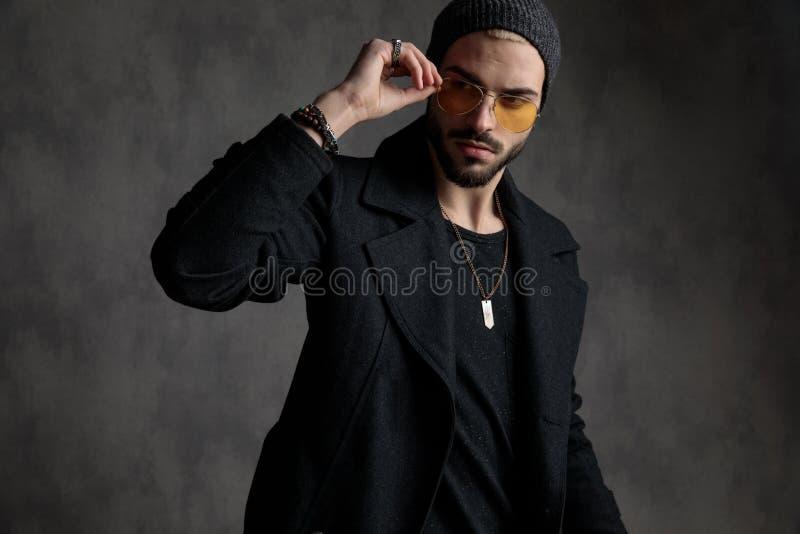 Homem bem vestido que arranja seus óculos de sol imagem de stock