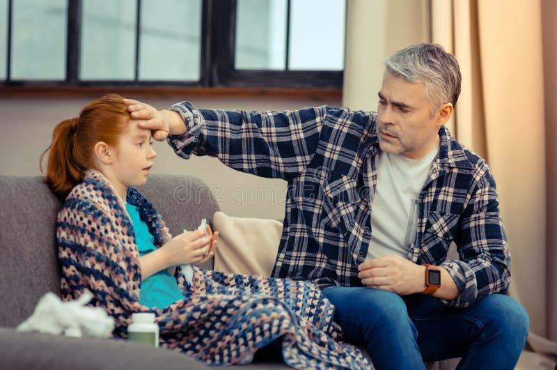 Homem bonito agradável que preocupa-se sobre sua filha imagens de stock