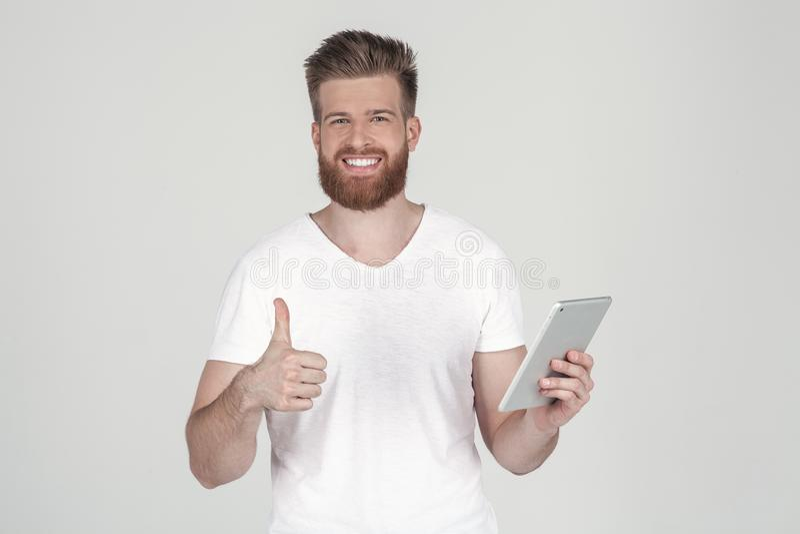 Homem bonito com uma barba e um penteado elegante vestidos na roupa ocasional sorrir mostra um polegar na parte superior e olha-o fotografia de stock