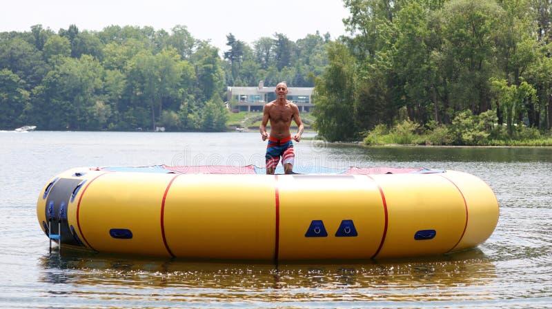 Homem bonito considerável que salta em um trampolim da água que flutua em um lago em Michigan durante o verão foto de stock